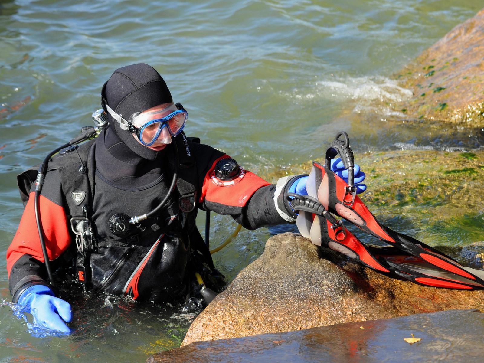 Der PADI Dry Suit Diver-Schüler bereitet sich auf seinen ersten Tauchgang im Trockentauchanzug vor.