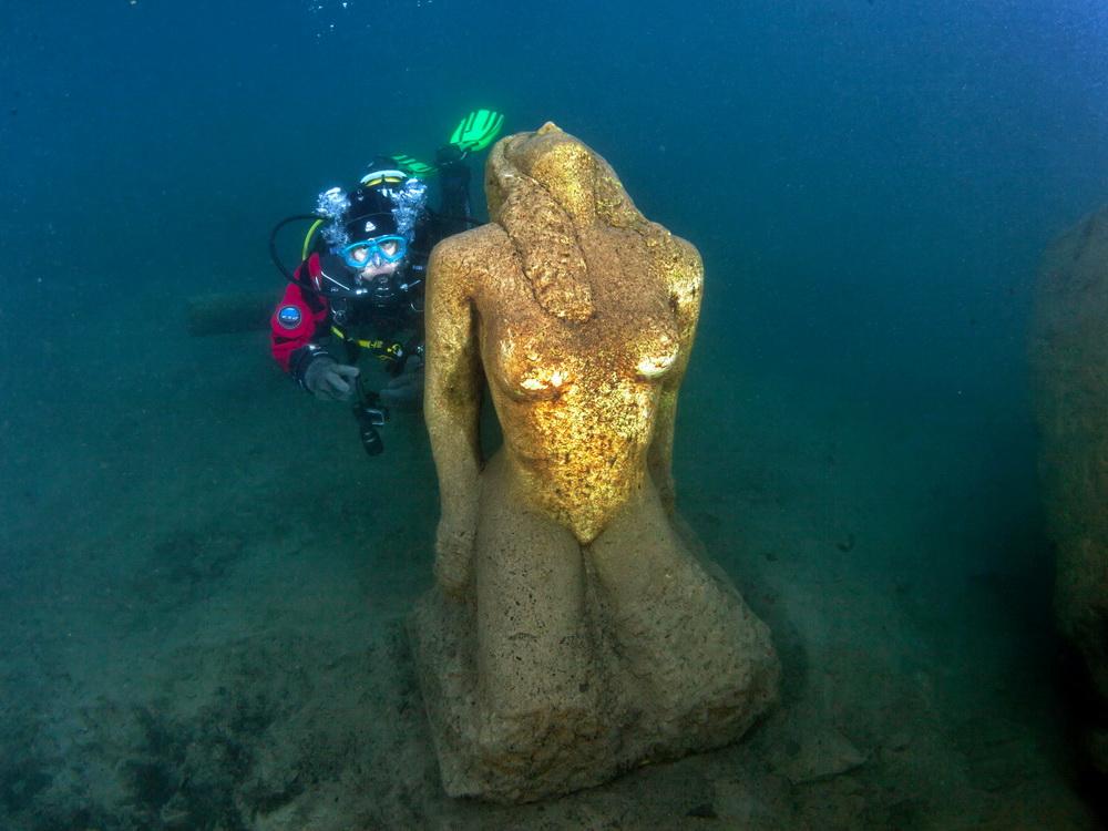 Taucher besucht die Statue im Blausee