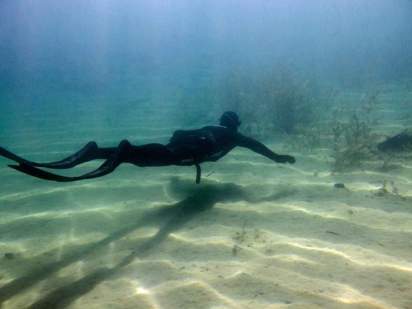 Apnoetaucher schwebt über den Sandboden
