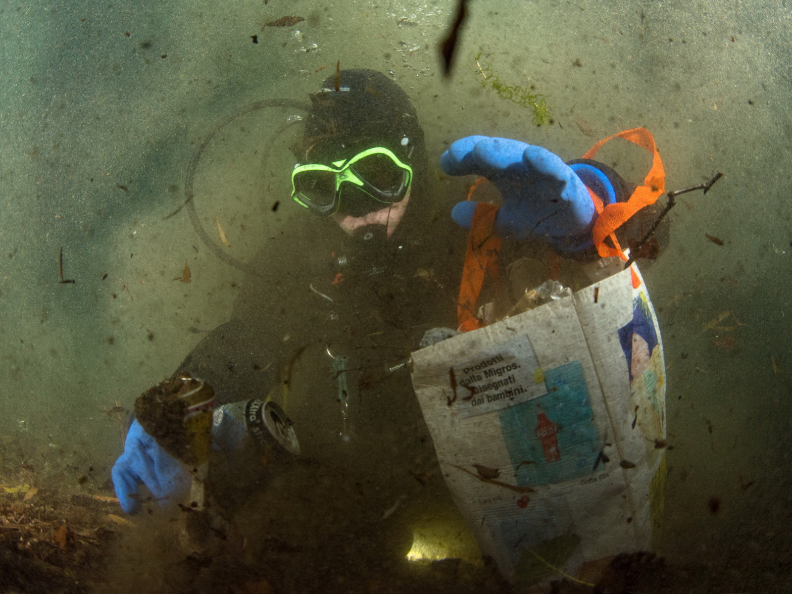 Taucher sammelt mit Einkaufsbeutel Müll