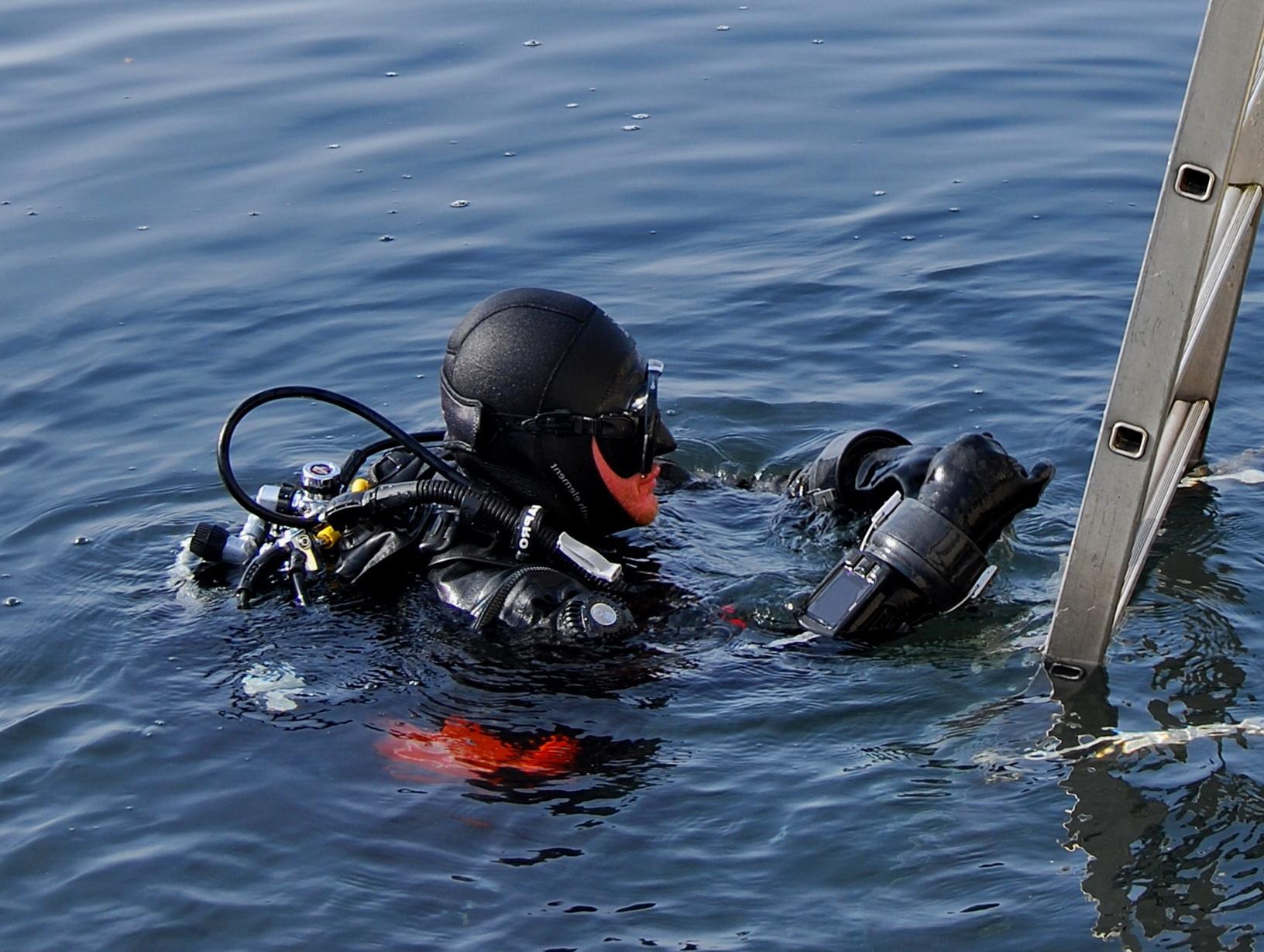 Taucher mit Trockentauchanzug beim Bootsausstieg