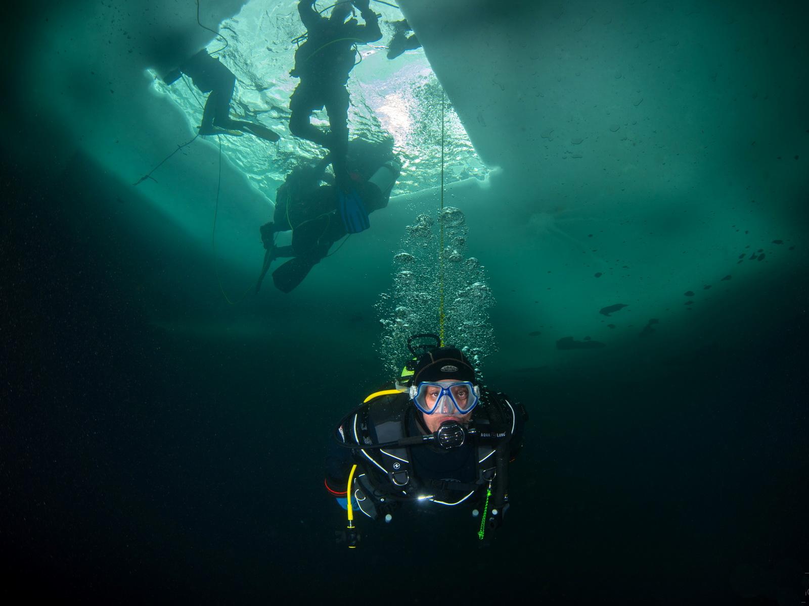 Taucher beim Abstieg durch das Loch in der Eisdecke