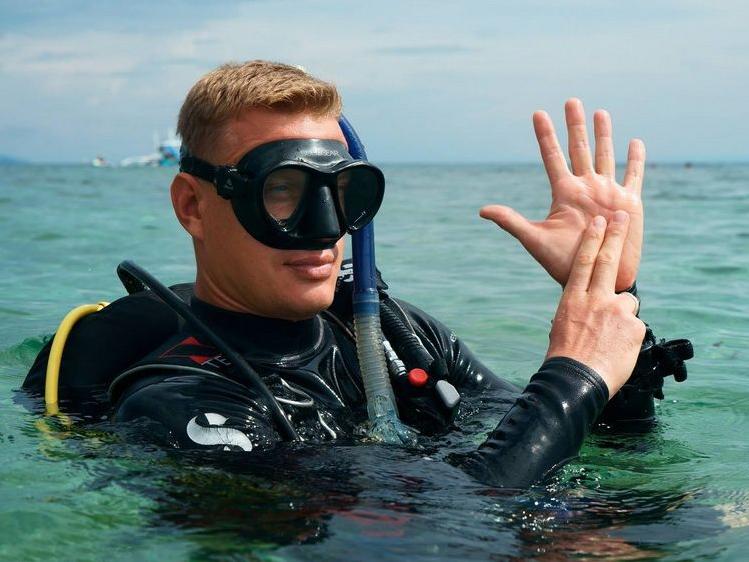 PADI Tauchlehrer zeigt Handzeichen