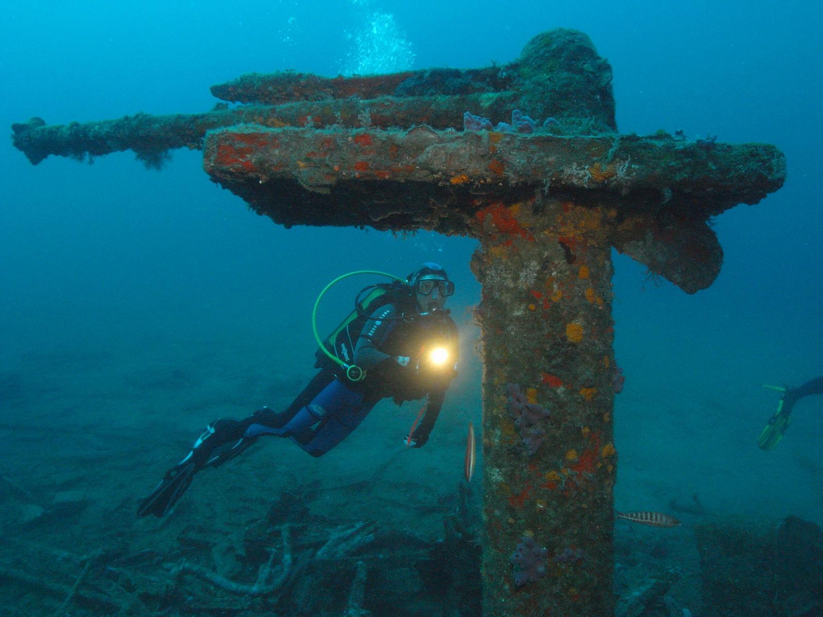 PADI Tieftaucher beleuchtet eine Unterwasserstruktur