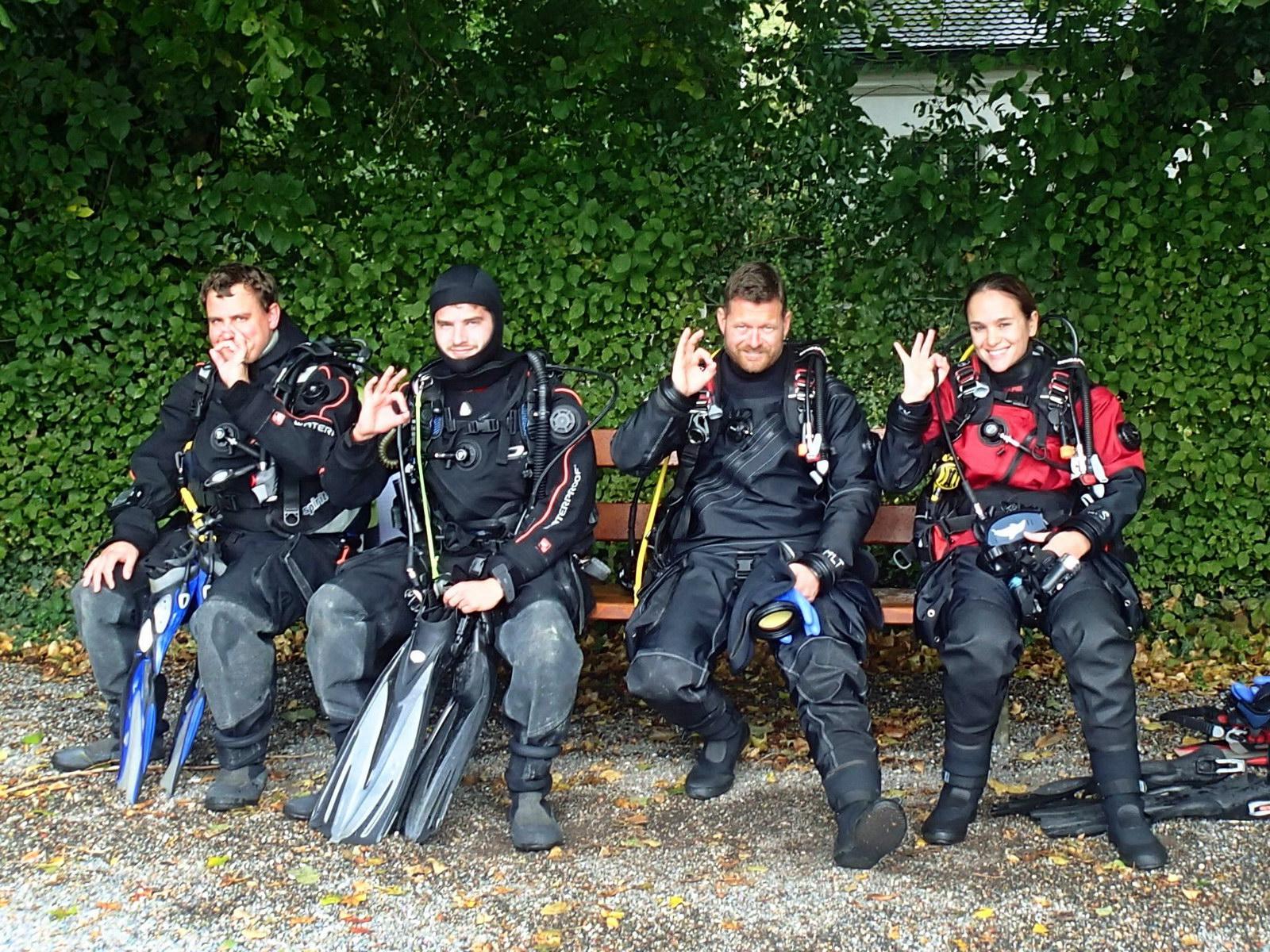 Vier SCUBA VIVA Trockentaucher sitzen in Warteposition
