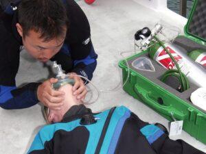 Taucherin wird mit Sauerstoff versorgt