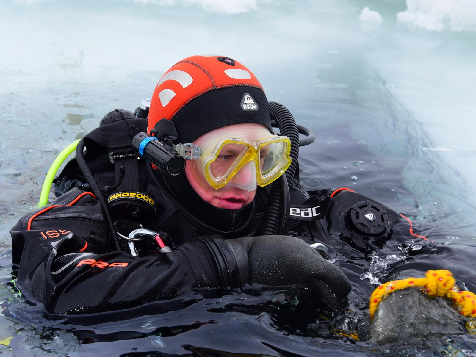 Taucher am Eisloch beim Abtauchen