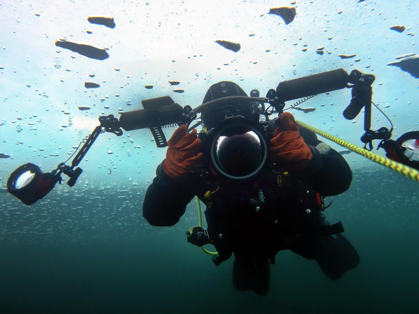 Taucher mit seiner Unterwasserkamera beim Eistauchen