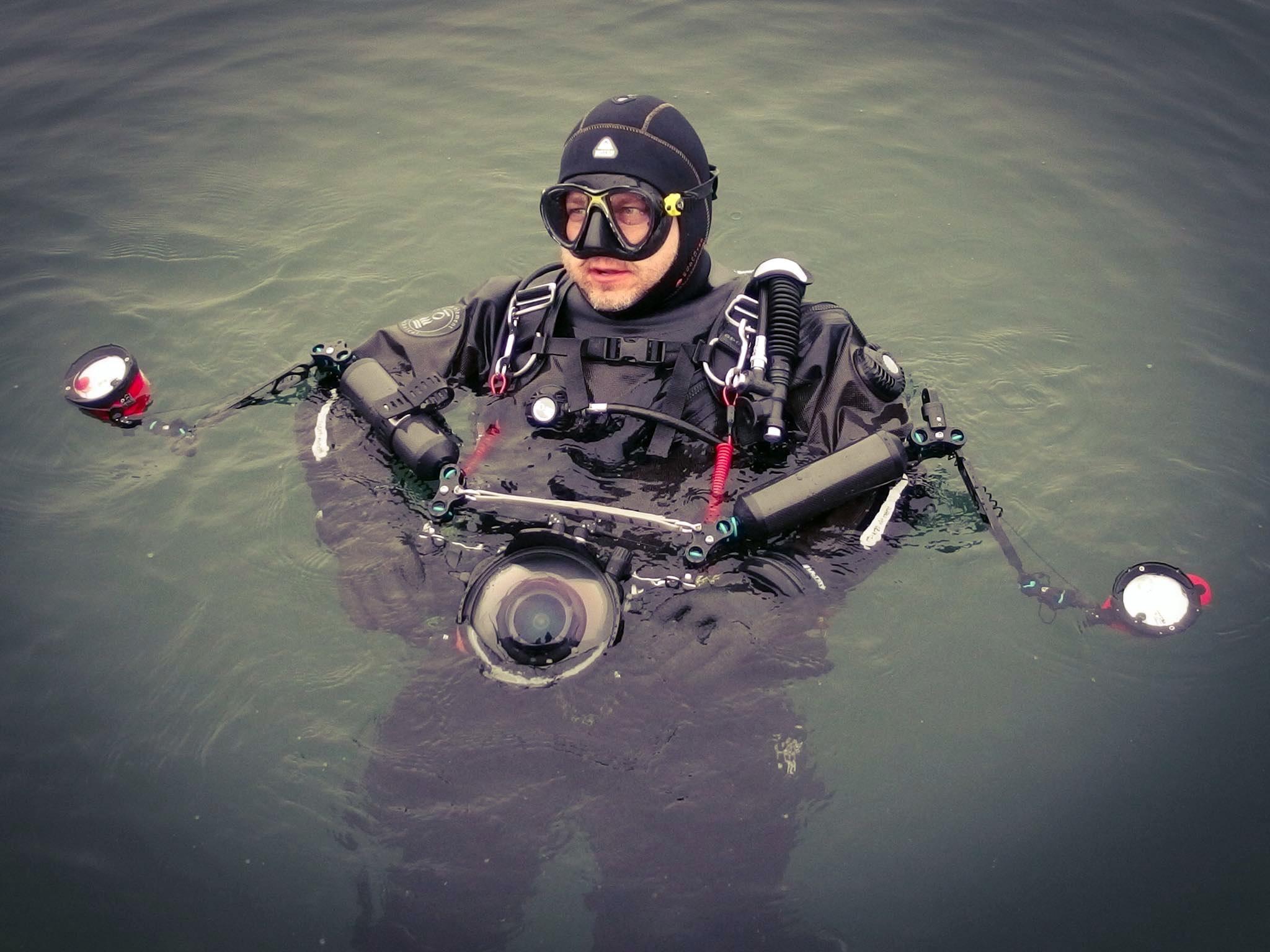 Tauchlehrer mit Unterwasserkamera beim Abtauchen