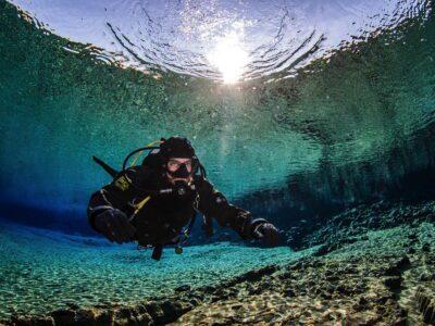 Solo Taucher schwebt im kristallklarem Wasser